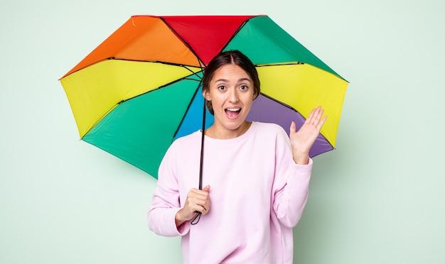 Junge hübsche frau, die sich über etwas unglaubliches glücklich und erstaunt fühlt. regenschirmkonzept