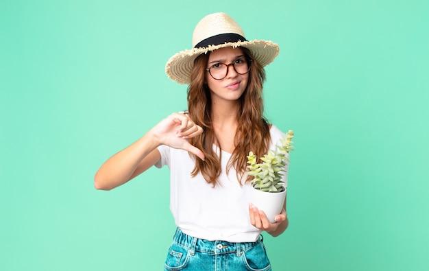 Junge hübsche frau, die sich überquert, daumen nach unten mit einem strohhut zeigt und einen kaktus hält