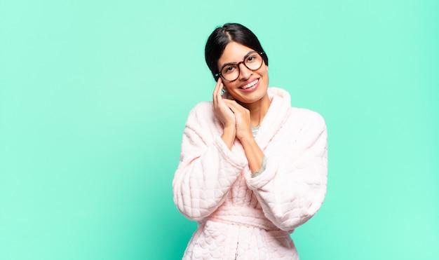Junge hübsche frau, die sich verliebt fühlt und niedlich, entzückend und glücklich schaut, romantisch mit händen neben gesicht lächelnd. pyjama-konzept