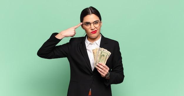 Junge hübsche frau, die sich verwirrt und verwirrt fühlt und zeigt, dass sie verrückt, verrückt oder verrückt sind. geschäfts- und banknotenkonzept