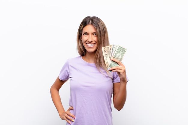Junge hübsche frau, die sich wie ein glückliches und aufgeregtes genie fühlt, nachdem sie eine idee verwirklicht hat, fröhlich finger hebend, eureka! mit banknoten