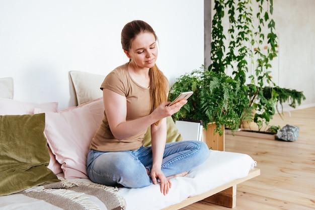 Junge hübsche frau, die smartphone zu hause sitzt auf sofa