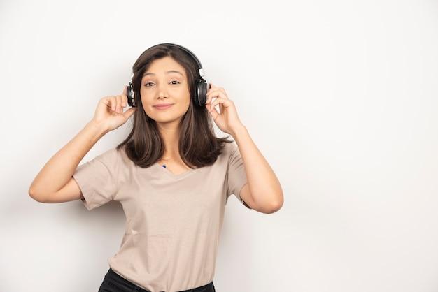 Junge hübsche frau, die spaß hat, musik durch drahtlose kopfhörer zu hören.