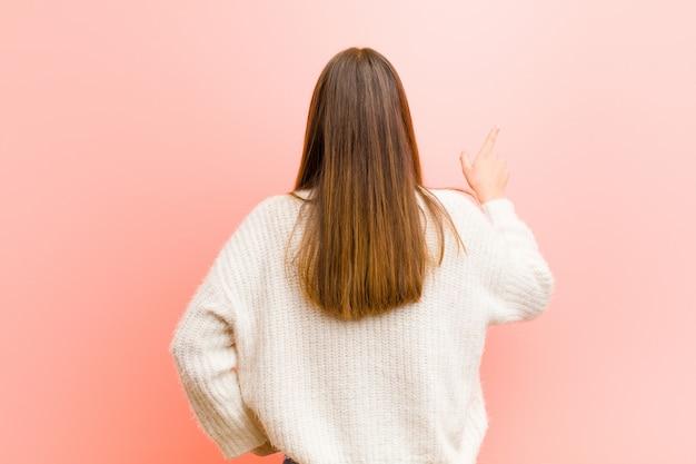 Junge hübsche frau, die steht und auf objekt auf kopienraum zeigt, rückansicht gegen rosa hintergrund