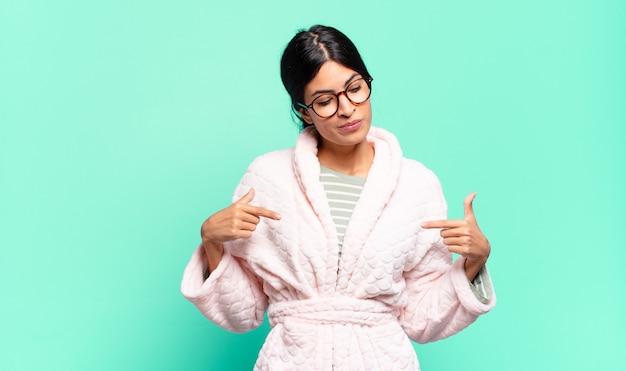 Junge hübsche frau, die stolz, positiv und lässig aussieht und mit beiden händen auf die brust zeigt. pyjama-konzept