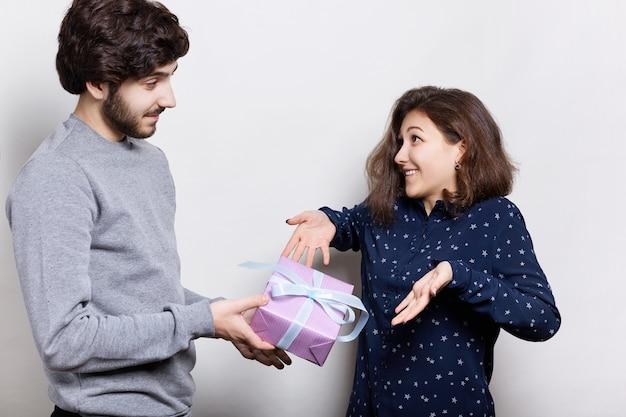 Junge hübsche frau, die überrascht ist, geschenk von ihrem freund zu erhalten. junges schönes paar, das nahe weißer wand steht