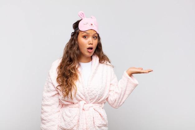 Junge hübsche frau, die überrascht und schockiert aussieht, mit gesenktem kiefer, der einen gegenstand mit einer offenen hand auf der seite hält, die pyjama trägt