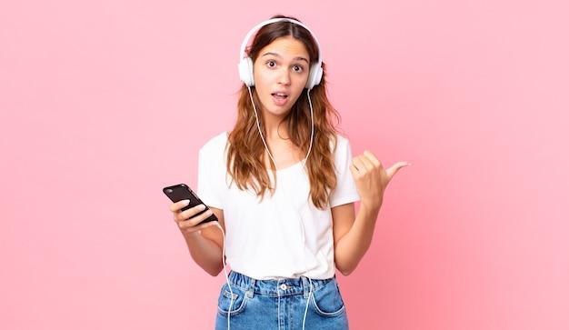 Junge hübsche frau, die ungläubig mit kopfhörern und einem smartphone schaut