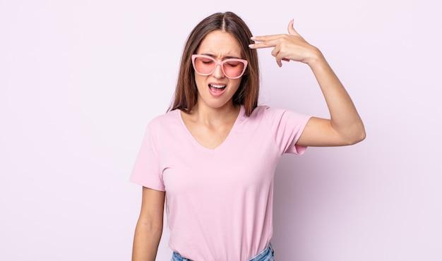 Junge hübsche frau, die unglücklich und gestresst aussieht, selbstmordgeste, die waffenzeichen macht. rosa sonnenbrillen-konzept