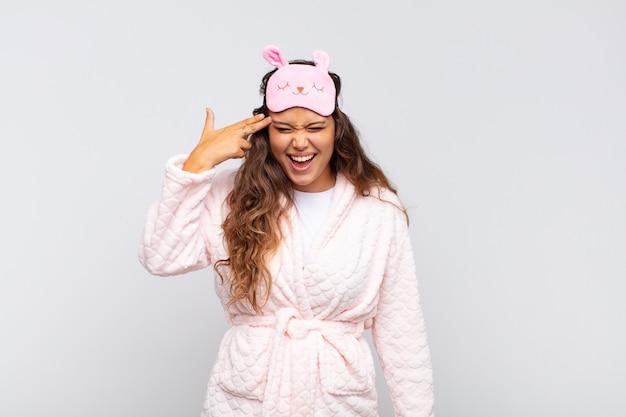 Junge hübsche frau, die unglücklich und gestresst aussieht, selbstmordgeste, die waffenzeichen mit der hand macht und auf den kopf zeigt, der pyjama trägt?