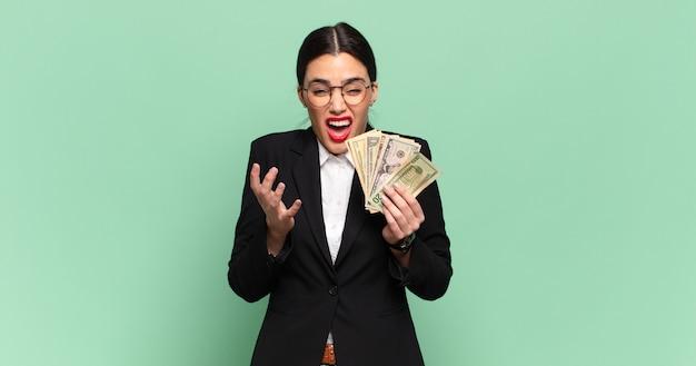 Junge hübsche frau, die verzweifelt und frustriert, gestresst, unglücklich und genervt aussieht, schreit und schreit. geschäfts- und banknotenkonzept