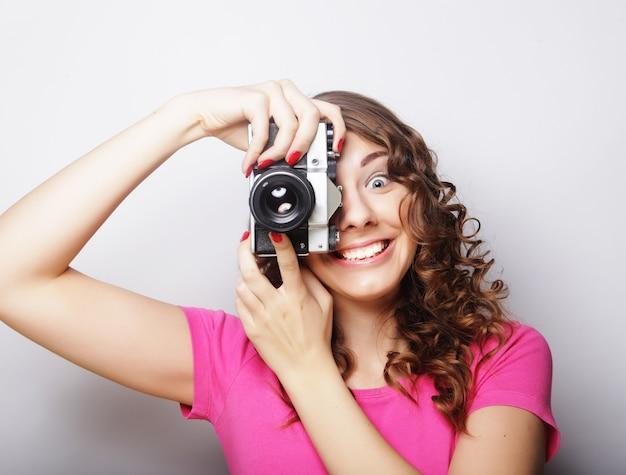 Junge hübsche frau, die vintage-kamera über grauem hintergrund hält.