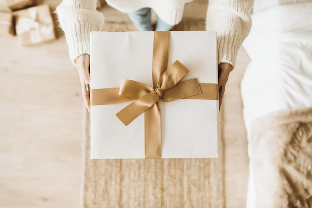 Junge hübsche frau, die weihnachts-neujahrsgeschenkboxen mit bögen hält