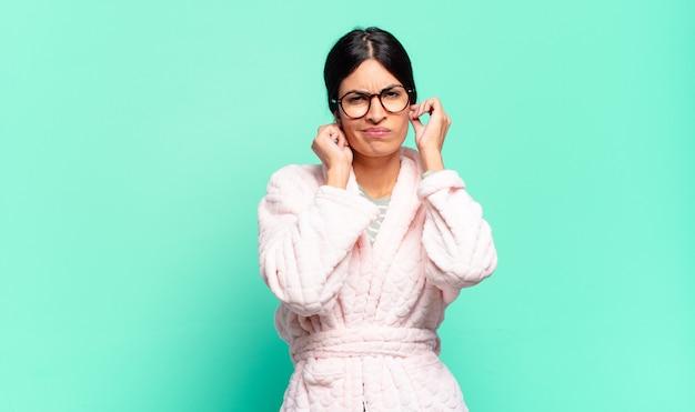 Junge hübsche frau, die wütend, gestresst und verärgert aussieht und beide ohren zu einem ohrenbetäubenden geräusch, ton oder lauter musik bedeckt. pyjama-konzept