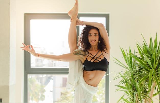Junge hübsche frau, die yoga drinnen praktiziert. entspannung und training