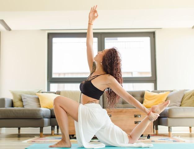 Junge hübsche frau, die yoga drinnen praktiziert