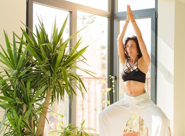 Junge hübsche frau, die yoga drinnen praktiziert.