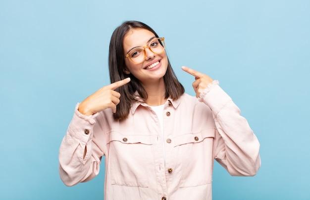 Junge hübsche frau, die zuversichtlich lächelt und auf eigenes breites lächeln, positive, entspannte, zufriedene haltung zeigt