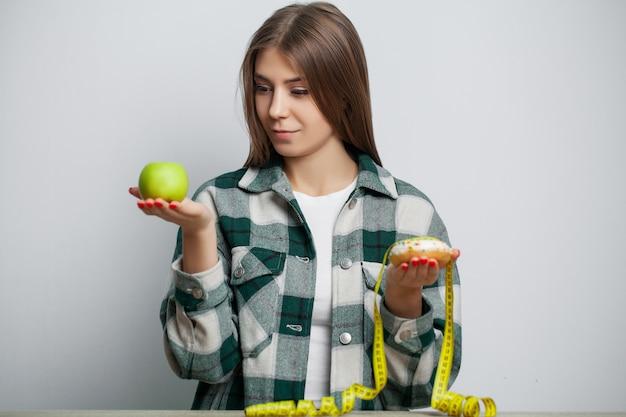 Junge hübsche frau hält an diät fest und wählt gesundes essen