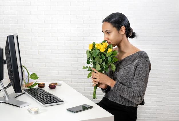 Junge hübsche frau hält einen strauß gelber rosen vor ihr gesicht und spricht online zu hause. technologiekonzept. neue normalität. valentinstag