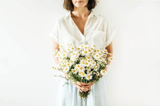 Junge hübsche frau halten in händen blumenstrauß der weißen kamille gänseblümchenblumen auf weißer oberfläche