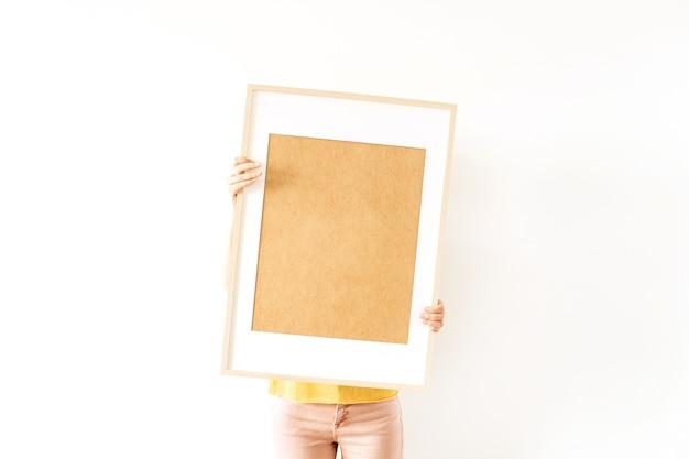 Junge hübsche frau halten leeren fotorahmen mit leerem kopienraum