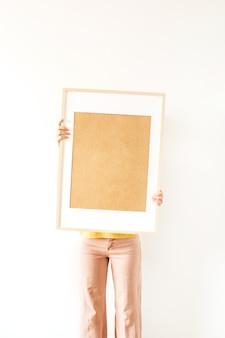 Junge hübsche frau halten leeren fotorahmen mit leerem modellkopierraum
