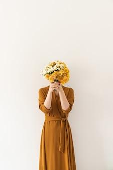 Junge hübsche frau im abendkleid des ingwers halten im handstrauß der gelben wilden blumen auf weißem hintergrund.