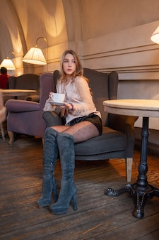 Junge hübsche frau im café. mädchen in einem café in einer beigen bluse. junges mädchen in einem café in schwarzen shorts und einer beigen bluse mit langen lockigen haaren. mädchen trinkt kaffee in einem café. latte, cappuccino