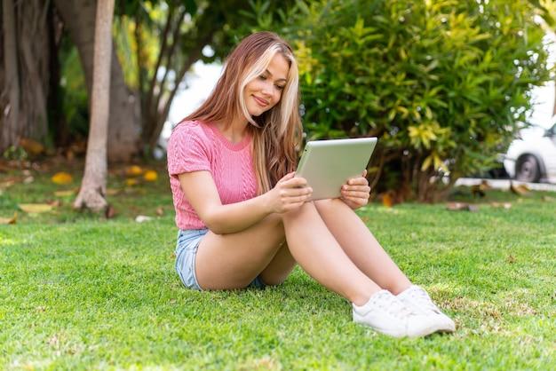 Junge hübsche frau im freien, die eine tablette hält