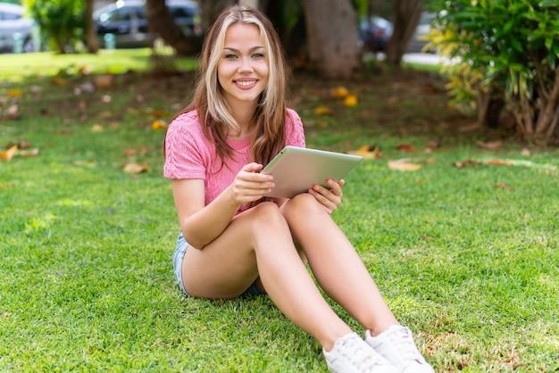 Junge hübsche frau im freien, die eine tablette mit glücklichem ausdruck hält