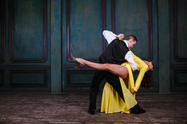 Junge hübsche frau im gelben kleid und im mann, der tango tanzt