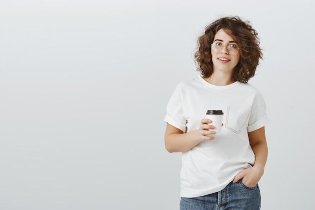 Junge hübsche frau im lässigen outfit, das kaffee auf arbeitspause trinkt