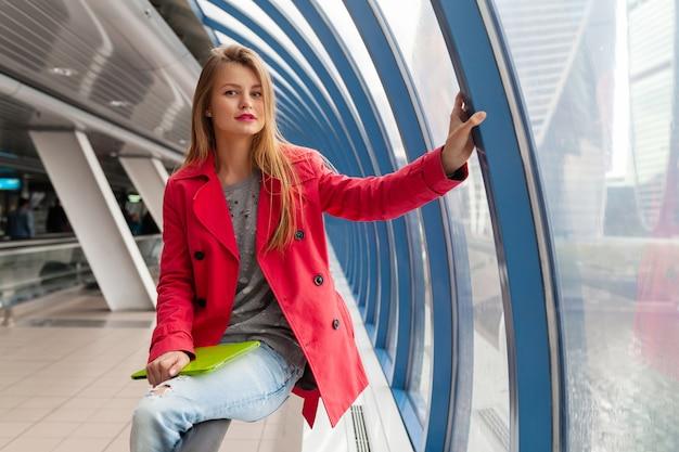Junge hübsche frau im lässigen outfit, das tablet-laptop im städtischen gebäude hält