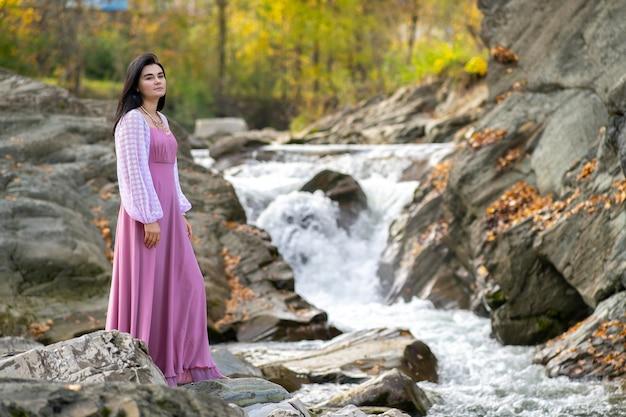 Junge hübsche frau im langen rosa modischen kleid, das nahe kleinem fluss mit sich schnell bewegendem wasser steht.