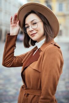 Junge hübsche frau im modernen brillen- und modehut und im braunen mantel wirft im stadtzentrum auf