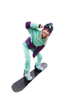 Junge hübsche frau im purpurroten skikostüm-fahrsnowboard