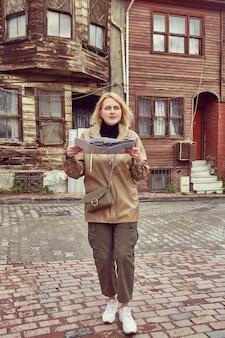 Junge hübsche frau im regenmantel reist in istanbul und versucht, ihren standort mit hilfe der karte zu finden