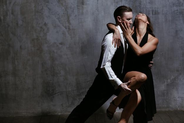 Junge hübsche frau im schwarzen kleid und im mann, der tango tanzt