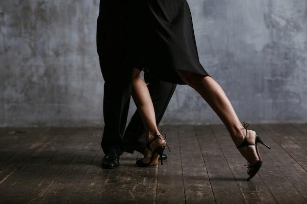 Junge hübsche frau im schwarzen kleid und im mann tanzen tango. beine schließen sich.
