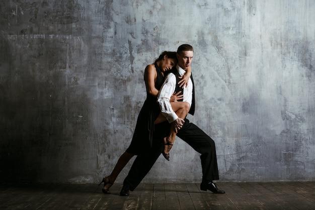 Junge hübsche frau im schwarzen kleid und im mann tanzen tango