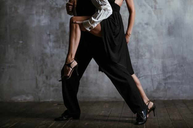 Junge hübsche frau im schwarzen kleid und mann tanzen tango