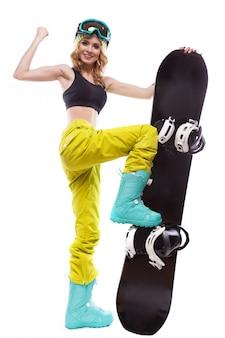Junge hübsche frau im schwarzen kurzen trägershirt und in den skigläsern halten snowboard