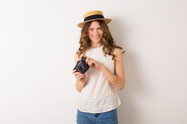 Junge hübsche frau im sommerferienart-outfit, das vintage fotokamera auf weiß hält