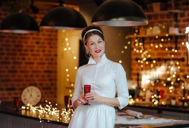 Junge hübsche frau im weißen langen kleid des retro-stils und im friseur mit band, das mit rotem glas wein in der küche mit weihnachtshintergrund aufwirft.