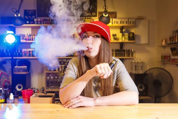 Junge hübsche frau in der roten kappe rauchen eine elektronische zigarette am vape shop