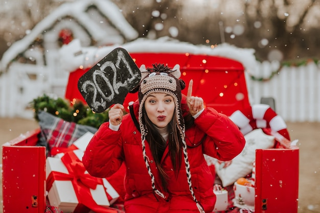 Junge hübsche frau in der roten winterjacke und in der strickmütze wie ein stier, der mit namensschild 2021 im offenen roten auto mit weihnachtsdekor aufwirft. es schneit.
