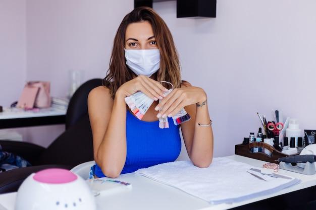 Junge hübsche frau in der schützenden medizinischen maske im nagelschönheitssalon mit erstaunlichem natürlichem weichem licht