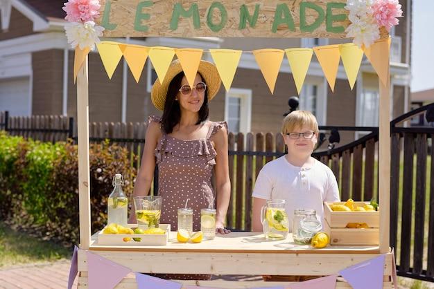 Junge hübsche frau in hut, kleid und brille und ihr kleiner sohn, der am hölzernen stand auf der straße steht und hausgemachte limonade verkauft