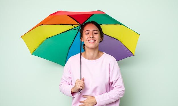 Junge hübsche frau lacht laut über einen urkomischen witz. regenschirmkonzept